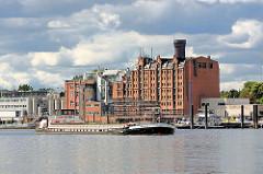 Ein Binnenschiff läuft von der Norderelbe in die Billwerder Bucht ein - im Hintergrund das historische Speichergebäude und Industrieanlagen am Ausschläger Elbdeich.