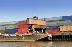 Güterumschlag am Kai des Tidekanals in Hamburg Billbrook; Schute an der Kaimauer - Transport eines Containers mit einem Hubwagen / Containertransport, Containerverladung.
