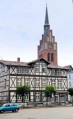 Historisches Wohnhaus / Geschäftshaus am Pferdemarkt in Grabow  - Fachwerhaus; Kirchturm der Kirche St. Georg.