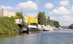 Motorboote am Ufer des Kanals - Gewerbehäuser; Gewerbegebiet in Hamburg Billbrook.