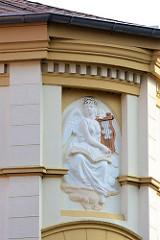 Bauschmuck an einem Gründerzeitgebäude - Figur mit Flügeln / Engel mit Harfe.