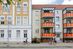 Historische und neue Architektur in Pritzwalk, Bahnhhofsstrasse - Gründerzeitarchitektur + Neubau mit rot verkleideten Balkons / neu + alt.