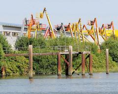 Hebebühne - Gewerbegebiet Hamburg Billbrook, Tidekanal. Metallpfähle / Dalben, Schiffsanleger mit Brücke.