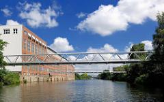 Lagergebäude / Speicher am Kanalufer des Billbrookkanals in Hamburg Billbrook - Leitungen führen über den Kanal - blauer Himmel, weisse Wolken.