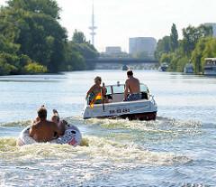 Motorboot mit Schlauchboot auf dem Bullenhuser Kanal in Hamburg Rothenburgsort - im Hintergrund der Fernsehturm der Hansestadt.