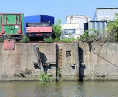 Kaimauer am Tidekanal in Hamburg Billbrook; Streichdalben aus Holz, verrottet - Eisenleiter in der Kaimauer; abgestellte LKW, Wohnwagen.