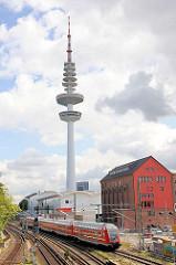 Blick über die Gleise an der Station Hamburg Sternschanze - ein Zug fährt ein; im Hintergrund der Hamburger Fernsehturm, Heinrich Hertz Turm.