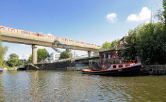Eisenbahnbrücke in Hamburg Rothenburgsort über den Billhornfer Kanal; Liegeplatz für Sportboote. Im Vordergrund die Bille kurz vor der Brandshofer Schleuse - Barkasse Ursula am Kai.