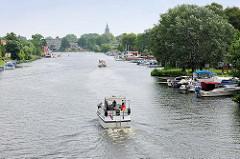 Blick auf die Brandenburgische Havel - ein Sportboot fährt Richtung Stadt Brandenburg an der Havel - Sportboote, Motorboote liegen am Ufer.