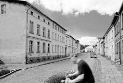 Einstöckige Wohnblocks, Etagenwohnungen im Hansensgang von Pritzwalk - Fahrradfahrer in Fahrt, Schwarz-Weiss-Fotografie.