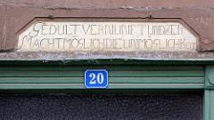 Sinnspruch im Holzbalken über dem Eingang eines Fachwerkhauses in Grabow: GEDULT VERNUNFT UND ZEIT MACHT MÖGLICH DIE UNMÖGLICHKEIT.