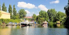 Sportboothafen am Ende des Billbrookkanals in Hamburg Billbrook; Motorboote liegen am Steg - Bäume am Ufer, blauer Himmel - weisse Wolken.