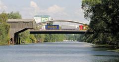 Strassenbrücke der Moorfleeter Strasse über den Billbrookkanal - Lastwagenverkehr; Kranausleger mit Holz verkleidet am Ufer des Kanals im Hamburger STadtteil Billbrook.