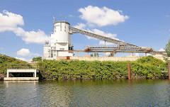 Schüttgutsilo mit Förderbändern am Ufer des Billbrookkanals im Gewerbegebiet von Hamburg Billbrook.