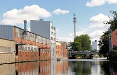 Gewerbegebäude mit Krananlage am Ufer vom Südkanal in Hamburg Hamm - im Hintergrund die Kanalbrücke am Grevenweg.