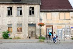 Leerstehende Wohnhäuser, zerbrochene Fensterscheiben / vernagelte Fenster - Blumenschmuck, Ampel mit roten Blumen am Laternenmast - Fahrradfahrer.