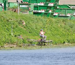 Angler am Ufer des Billbrookkanals in Hamburg Billbrook - Container im Hintergrund.