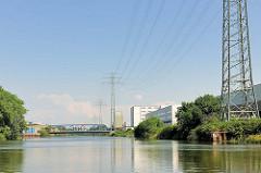 Hochspannungsleitungen, Hochspannungsmasten entlang des Tidekanals in Hamburg Billbrook; im Hintergrund die Brücke der Moorfleeter Strasse.