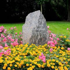 Gedenkstein für den Antifaschisten ERNST HENKEL 1887 - 1944 in Pritzwalk; blühende Blumen, Blumenbeet.