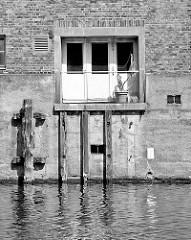 Streichdalben aus Holz, verrottet / zerfressen an der Kanalseite des Billbrookkanals - Ladetür zur Wasserseite des Speichergebäudes.