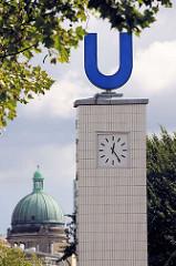 U-Bahnstation Hamburg Feldstrasse - Uhrenturm mit grossem U; Kachelfassade. im Hintergrund die Kuppel vom Oberlandesgericht am Sievekingplatz.