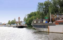 Binnenschiff und Sportboote am Ufer der Bille in Hamburg Billbrook - im Hintergrund der unter Denkmalschutz stehende Commentz - Turm.