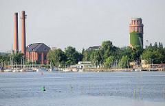 Blick über den Plauer See zum Industriegebiet des Ortsteil Kirchmöser / Brandburg a. d. Havel. Hohe Fabrikschornsteine - Wasserturm; Marina am Ufer des Sees.