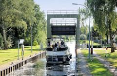 Schleuse vom Elde-Müritz-Wasserweg in Parchim; das Signallicht zeigt Grün, ein Sportboot verlässt die Schleusenkammer.