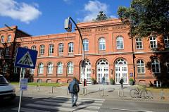 Backsteinarchitektur in Hamburg - altes Eingangsgebäude, Eingang zum Krankenhaus Eppendorf - Universitätsklinik - Fussgänger auf dem Zebrastreifen.
