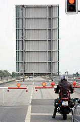 Geöffnete Klappbrücke am Störsperrwerk an der Bundesstrasse 431 - der Mast eines Segelschiffs ist bei der Durchfahrt zu erkennen.