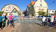 Bei Schleusung mit Schranken gesperrte Brücke der Mühlenstrasse in Lübz - Passanten warten auf die Öffnung der Absperrung.