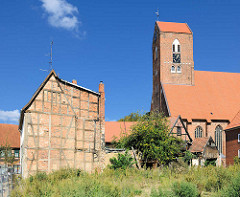 St. Georgenkirche - Pfarrkirche der Altstadt von Parchim; Ursprungsbau von 1289 - dreischiffiger gotischer Backsteinbau. Fassade eines alten Fachwerkhauses - Ziegelmauer / Wiese.