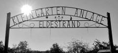 Metallschild / Schrift und Verzierung; Kleingarten Anlage Eldestand - Sonne / Gegenlichtaufnahme, Schwarz-Weiss.