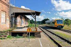 Einfahrt eines Nahverkehrszugs am Bahnhof Neustadt Glewe; das Bahnhofsgebäude ist stillgelegt; Rampe des Güterbahnhofs - Schild Zutritt verboten.