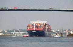 Der Containerfrachter APL MERLION auf der Süderelbe in Fahrt zum Hamburger Container Terminal Altenwerder - der 368m lange Megaboxer kann 14 000 TEU Container an Bord nehmen. LKW mit Containern fahren auf der Köhlbrandbrücke.
