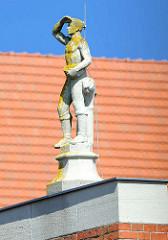 Figur auf dem Dach eines denkmalgeschützten Wohn- und Geschäftshause am Schuhmarkt in Parchim. Steinfigur blickt mit Hand über den Augen in die Ferne.