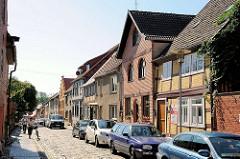 Wohnhäuser in der Mühlenstrasse, Plau am See; parkende Autos - Kopfsteinpflaster.