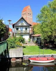 Wohngebäude am Wassergang an der Elde in Parchim - rotes Ruderboot am Ufer; Kirchturm der St. Marienkirche.