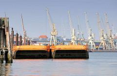 Arbeitsschuten im Hansahafen; historische Hafenkräne am Bremer Kai vom Hafenmuseum Hamburg.