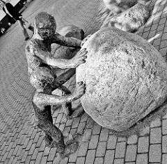 """Kunst im Öffentlichen Raum; Marktplatz Henstedt-Rhen - """"Anschieben"""", Grossplastik  2006; Bildhauer Thoma Behrend."""