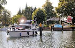 Ein Sportboot verlässt die Schleusenkammer in Plau am See - Fussgängerbrücke mit Zuschauern.