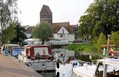 Sportboothafen / Marina in Parchim, Elde-Müritz-Wasserweg; Motorboote an Liegeplätzen mit Stromanschluss - im Hintergrund der Kirchturm der Parchimer Marienkirche.