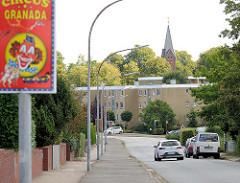 Blick vom Schäferberg in Henstedt-Ulzburg; Ankündigungschild für einen Zirkus - im Hintergrund Neubauten gelber Klinker und der Kirchturm der Henstedter Erlöserkirche.