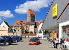 Parkplatz eines Supermarktes - parkende Autos; im Hintergrund Häuser und Kirchturm der Neustadt in Parchim, Mecklenburg Vorpommern.