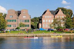 Wohnhäuser am Alsterufer in Hamburg Winterhude - Kanus auf dem Wasser, Menschen in der Sonne am Alsterufer.