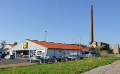 Supermarkt mit Parkplatz - im Hintergrund verfallenes Fabrikgebäude, Fabrikschornstein.