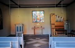 Innenansicht der Stiftskirche zu Lübz; Sitzbänke, Altar und Buntglasfenster.