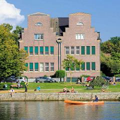 Blick vom Haynspark in Hamburg Eppendorf über die Alster nach Winterhude - ein Holzkanu fährt auf der Alster, Menschen in der Sonne am Alsterufer.