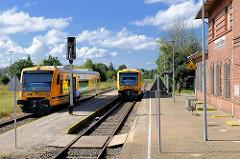 Nahverkehrszüge am Bahnhof Neustadt Glewe; das Bahnhofsgebäude ist stillgelegt.
