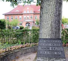 Friedenseiche an der Dorfstrasse von Henstedt / Henstedt-Ulzburg, im Hintergrund das Schulgebäude. Inschift des Gedenksteins: Zur Friedensfeier Gesetzt von der COMMUNE HESTEDT den 22. März 1871.